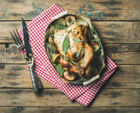 Oven roasted whole chicken in tray over wooden background Stock Images