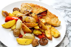 Oven vegetables and baking shred. Vegetables baked in the stove, consisting of potatoes, champignons, paprika, onions, garlic. In addition there is a pork with Royalty Free Stock Photography