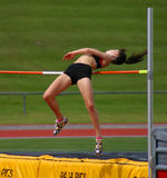 Over the bar. Young Girl attempting a high jump royalty free stock photos