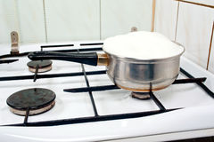 Over boiling milk. Over boiling ( brimming ) milk in a pot on stove Royalty Free Stock Photography