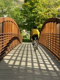 Over the Bridge. Bicyclists pedal over pedestrian bridge in Fall Stock Photography