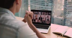 Over businessman shoulder laptop view partners involved in videoconference negotiations