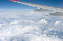 Over the Clouds. Wing of a plane with wide view over the clouds Stock Photo