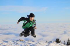Over the clouds. Child jumping in the air over the clouds Stock Photos