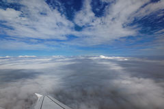 Over the clouds. Out of an aeroplane window, visible wing Royalty Free Stock Photos