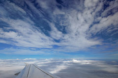 Over the clouds. Out of an aeroplane window, visible wing Stock Images