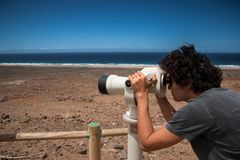 A young man using a tower viewer in Cofete beach, Fuerteventura, Canary Islands. stock photos
