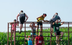 Over coming obstacles in your way. Athletes participating in the 2014 mudathlon have to run jump and climb over other obstacles in their way along this course stock photo