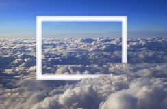 Over cumulus clouds bright landscape view from the window of an airplane with a white frame.  royalty free stock images