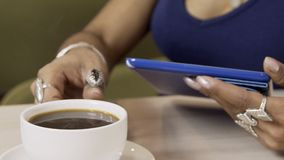 Over cup of hot coffee afro female figure close-up is holding a tablet. stock video