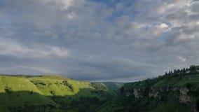 Over de groene canion die langzaam wolken drijven bij zonsondergang stock video