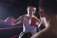 Over de schoudermening van twee mannelijke boksers die in de boksring in Peking, China vechten Stock Foto's