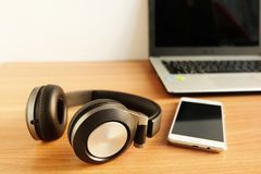 Over-Ear Headphone and smart phone with laptop on wooden floor. Used electronics gadgets stock image