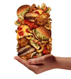 Over Eating. And compulsive indulgence of fast food concept as a hand holding up a huge stack of junk food as hamburgers hotdogs and french fries as an Royalty Free Stock Images
