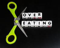 Over eating. Cut down on `over eating` with text on small white cubes and scissors to imply reduction and keep slim not overweight, dark background royalty free stock images