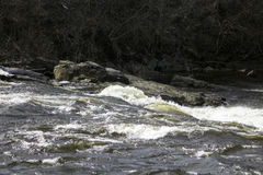 Over the Edge. Fast flowing water on the Grasse river creating rapids as it goes over the rocks in the bed Stock Photos