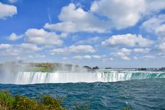 Over the Edge of Niagara Falls. A view of the Horseshoe falls from the Niagara Falls, Canada side. It`s a spectacular and exhilarating sight under a beautiful stock photo