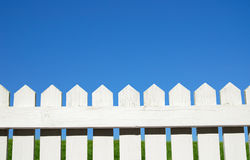Over the fence. White picket fence, green grass and sky stock photography