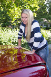 Over filled trunk. A young woman struggles to shut the trunk of her car that she has overfilled Royalty Free Stock Photos