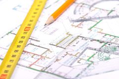 Over the floor plan. Tape measure, pencil and other tools on top of floor plan stock image