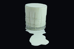 Over flow. An glass of milk that overflowed against a black back ground Stock Photos