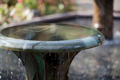 Over Flowing Bird Bath. An over flowing bird bath caught mid drip as water cascades over the edge Royalty Free Stock Photography