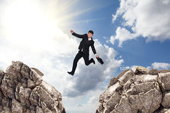 Over gap. Image of young businessman jumping over gap Royalty Free Stock Image