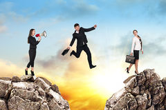 Over gap. Image of young businessman jumping over gap at the sunset Royalty Free Stock Image