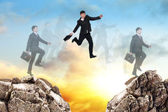 Over gap. Image of young businessman jumping over gap at the sunset Royalty Free Stock Photography
