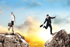Over gap. Image of young businessman jumping over gap at the sunset Stock Photo