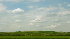 Over green hills, white cumulus clouds fly in the blue sky. time interval. Over green hills, white cumulus clouds fly in blue sky. time interval stock footage