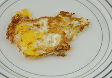 Over Hard Fried egg on plate. Close up of over hard fried egg on plate against off white background Stock Images