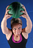 Over Head Lift. Pretty young woman lifting a green medicine ball over her head Royalty Free Stock Photography