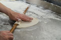 Over head view of a grandmother`s hands rolling out pasty dough. stock image