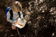 Little girl with backpack sitting on ground writing in notebook. Over head view of little girl with backpack sitting on ground writing in notebook Stock Images