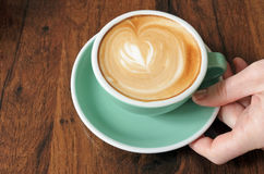 Over head view of woman hand holds a flat white cup of coffee dr Stock Photos