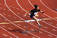 Over a hurdle. LAKE STEVENS, WA - MAY 07, 2012:an woman athlete jumping over a hurdle on a track at Lake Stevens High School, Lake Stevens, Washington, USA Stock Images