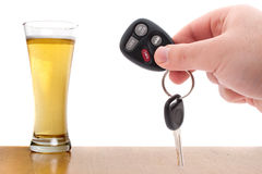 Over The Limit. Drunk driving concept image with a hand holding some car keys and a glass of beer isolated over a white background Royalty Free Stock Photo