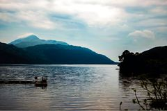 Beautiful moody Loch Lomond. Over looking the beautiful and moody Loch Lomond and still water in The Trossachs National Park, with clouds rolling on top of the Stock Images