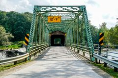 Over One Hundred Years Old. This is Harpersfield Covered Bridge that spans the Grand River in northeast Ohio the bridge is over a hundred years old and cars Stock Images