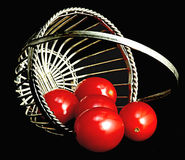 Over and Out. Little over-turned basket with tomatoes spilling out Stock Image