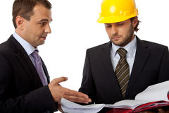 Over the plans. Two business people, one with helmet are looking at plans Royalty Free Stock Photography