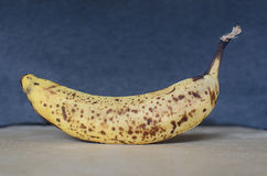 Over Ripe Spotted Banana. On wood surface Royalty Free Stock Photos