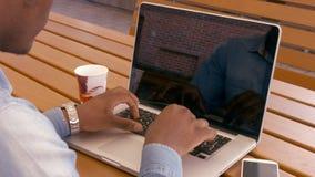 Over schoudermening van de mens die laptop met behulp van stock videobeelden