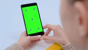 Woman looking at black smartphone device with empty green screen. Over shoulder close up view - woman looking at black digital smartphone device with empty green stock footage