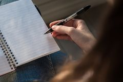 Woman seated with open notebook in lap and holding pen in hand royalty free stock images