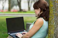 Over shoulder look of young woman with laptop Royalty Free Stock Photo