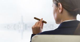 Over shoulder of seated business woman smoking cigar and looking at blurry white skyline. Digital composite of Over shoulder of seated business woman smoking Royalty Free Stock Image