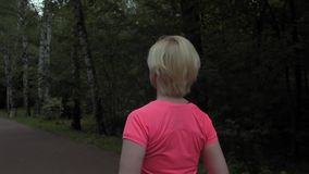 Over the shoulder of serious woman running in the dark park while cloudy day. Over the shoulder shot of serious woman running in the dark park while cloudy day stock video footage