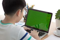 Over the shoulder shot of an Asain boy typing on a computer lapt. Op with a key-green screen. Woman hand typing laptop with green screen Royalty Free Stock Image